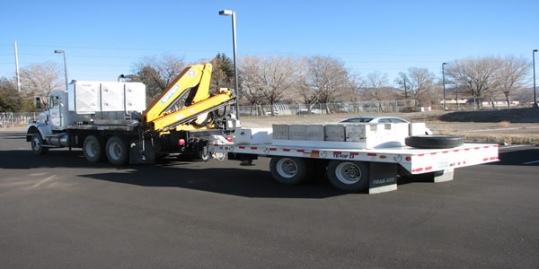 Flat bed truck with loader pulling trailer